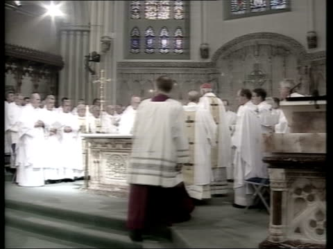 Cardinal Winning funeral ITN Clergy gathered for funeral around altar Priests kissing altar TGV Interior of cathedral Cardinal Winnings hat on the...