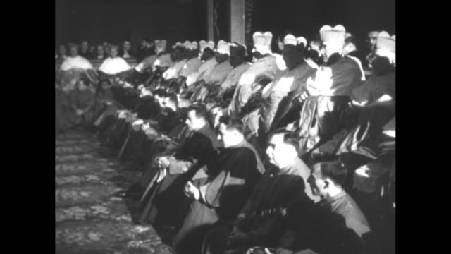 vidéos et rushes de cardinals standing in two rows, several cardinals lie prostrate on carpet / vs cardinals sitting in two rows, back row higher and wearing caps and... - châle