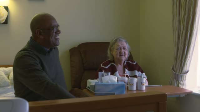 care minister calls on people to look after elderly relatives england int raymond james along corridor and into room to visit elderly mother in care... - ジャッキー ロング点の映像素材/bロール