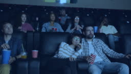 Carefree adults watching film in modern cinema holding drinks and snacks