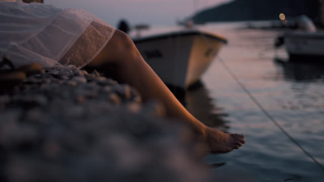 cu carefree barefoot woman dangling legs over ocean,adriatic sea,croatia - moor stock videos & royalty-free footage