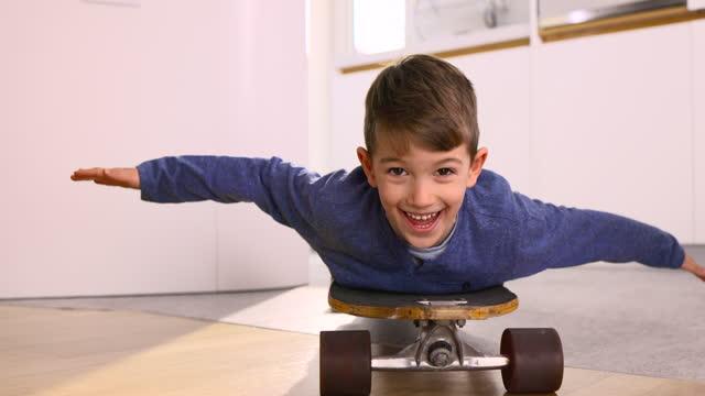 vídeos y material grabado en eventos de stock de chico despreocupado divirtiéndose en un monopatín en casa. - acostado
