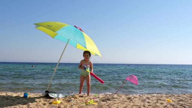 carefree child playing with a water gun on the beach - parasol stock videos & royalty-free footage
