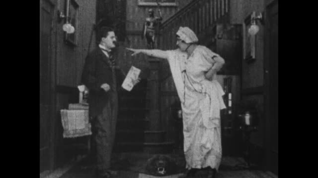 1915 carefree edwardian husband comes downstairs and greets argumentative wife while lazy maid stands by - husband stock videos & royalty-free footage