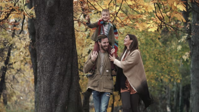 carefree family having fun while enjoying in autumn day at the park. - carrying on shoulders stock videos & royalty-free footage
