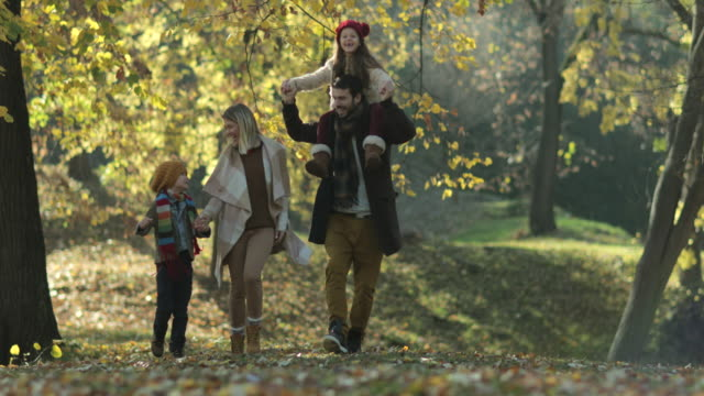 Carefree family running in the park and having fun in autumn day.