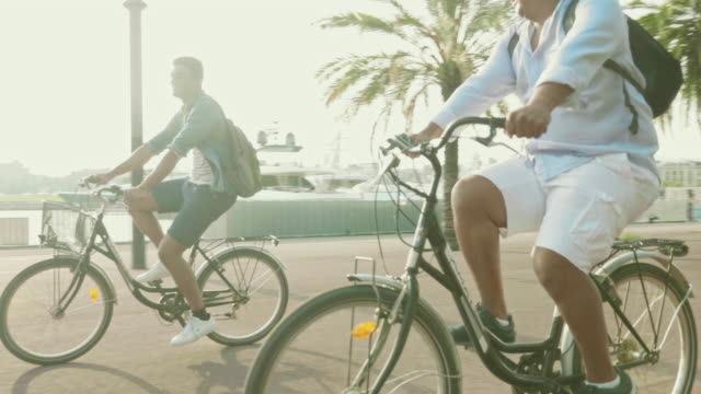 carefree father and adult son having fun on rental bikes - modern manhood stock videos & royalty-free footage