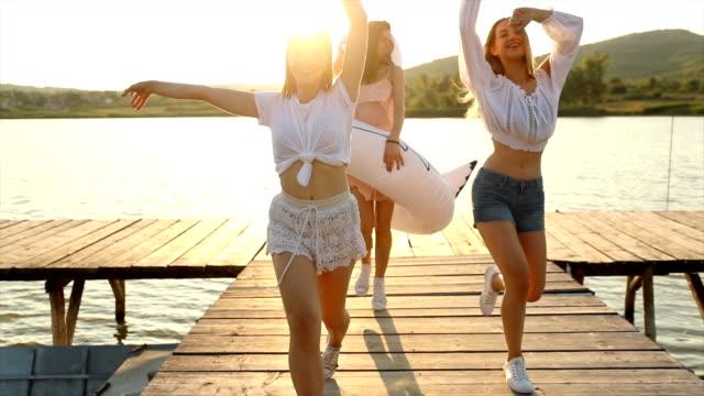 vidéos et rushes de amis féminins insouciants ayant l'amusement sur le lac avec le cygne gonflable - cygne
