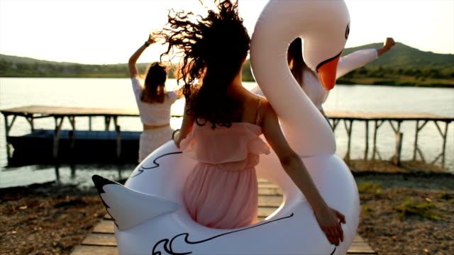 vídeos y material grabado en eventos de stock de despreocupadas amigas divirtiéndose en el lago con el cisne inflable - brazo humano