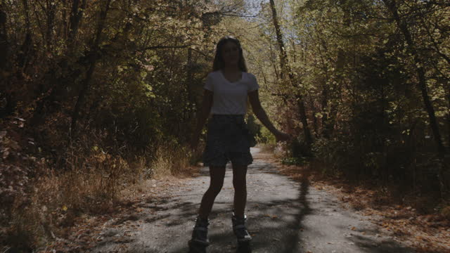 carefree girl inline skating and listening to headphones on park path in autumn / american fork canyon, utah, united states - american fork canyon stock videos & royalty-free footage