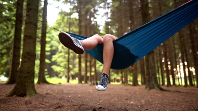 carefree girl lying in a hammock enjoying the day in a forest - hammock stock videos & royalty-free footage