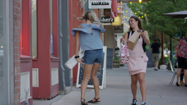 carefree girls carrying shopping bags dancing on city sidewalk / provo, utah, united states - provo stock videos & royalty-free footage