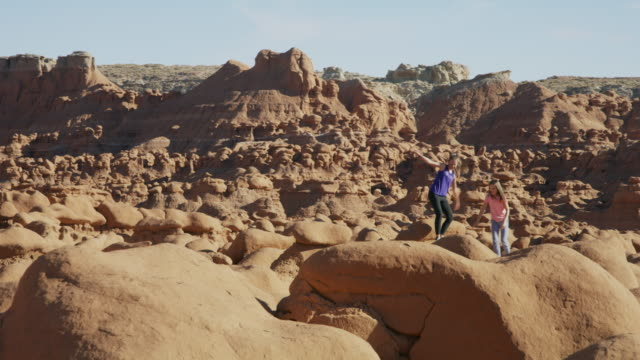 vidéos et rushes de carefree girls hiking on rock formations in desert / goblin valley, utah, united states - children only