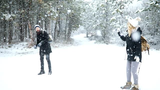 unbeschwerte junge brautpaar spaß zusammen im schnee im winter wald werfen schneebälle auf einander, während ein scheingefecht - wintermantel stock-videos und b-roll-filmmaterial