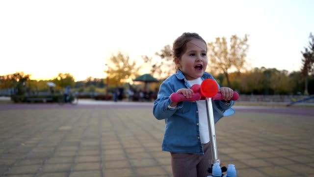carefree little girl enjoys riding a toy push scooter - 2 3 years stock videos and b-roll footage