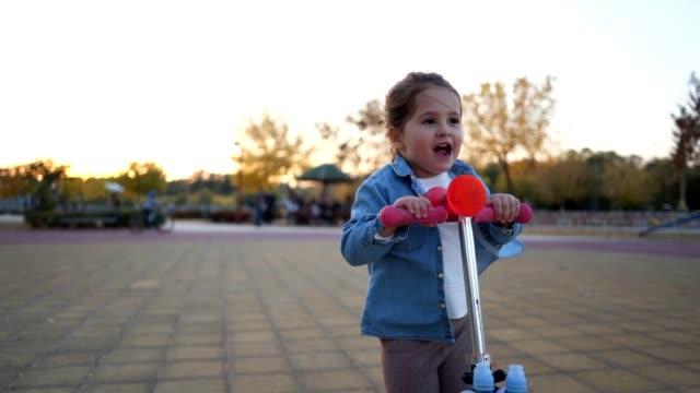 vídeos de stock, filmes e b-roll de menina despreocupada goza de montar uma scooter de empurrão de brinquedo - 2 3 anos