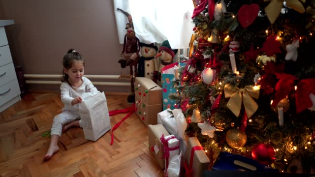 carefree little girl unwrapping her presents - unwrapping stock videos & royalty-free footage
