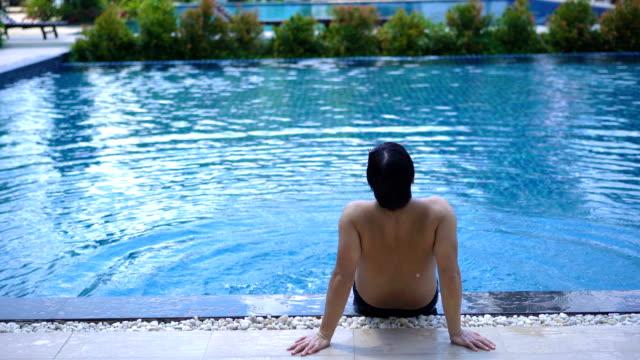 vídeos y material grabado en eventos de stock de hombre sin preocupaciones disfrutando de su tiempo en la piscina - bañador de natación