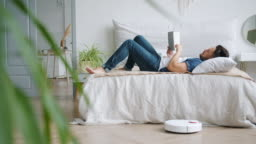Carefree man reading book in bed while robotic vacuum cleaner vacuuming floor