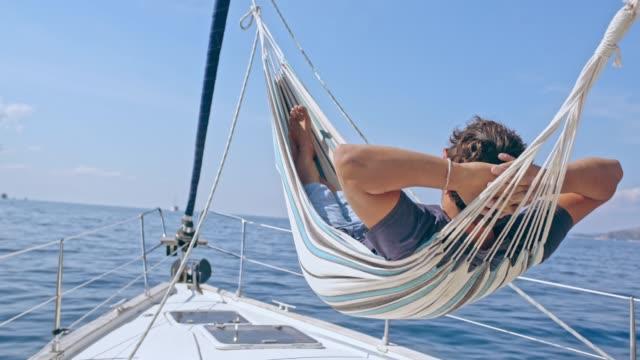 vídeos y material grabado en eventos de stock de 4k hombre despreocupado en hamaca en velero soleado, tiempo real - hamaca