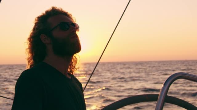 4K sorglos Mann Segeln auf sonnigen, ruhigen Sonnenuntergang Ozean, Slow-motion
