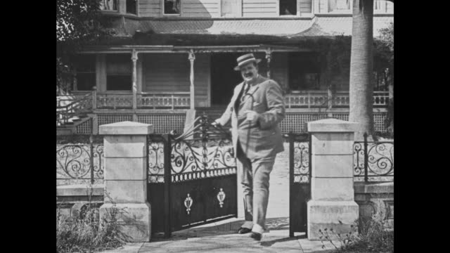1921 Carefree man (Joe Roberts) walks down the front steps of his mansion, twists his moustache and proceeds down the street