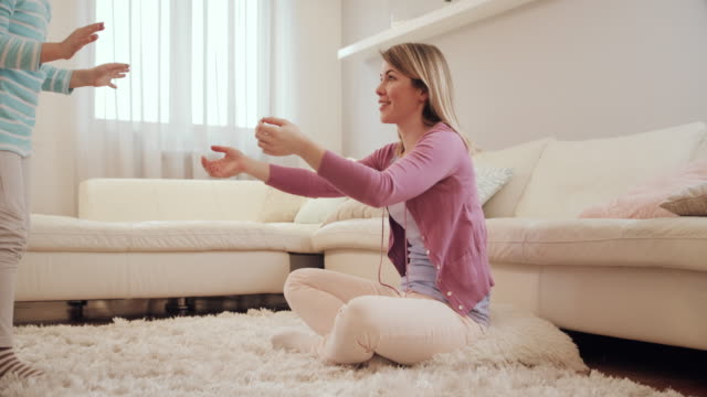 carefree mother and daughter having fun while playing at home. - fare il solletico video stock e b–roll