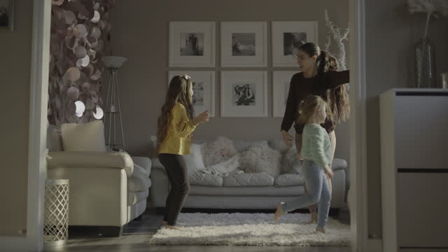 carefree mother and daughters dancing in livingroom / south jordan, utah, united states - singen stock-videos und b-roll-filmmaterial