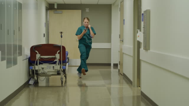 Carefree nurse skipping to music then surprised by doctor in corridor / Salt Lake City, Utah, United States