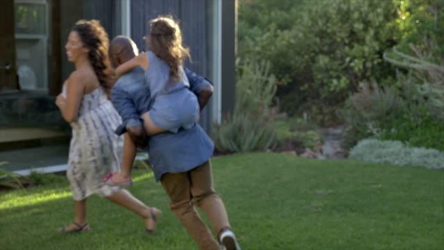 vidéos et rushes de carefree parents playing with daughter in yard - parents