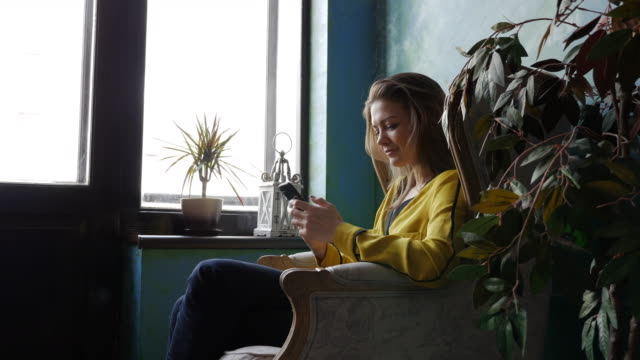 Unbeschwerte positive Brünette in einem Sessel mit einem smartphone