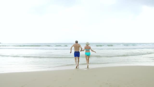 vídeos de stock, filmes e b-roll de casal sênior despreocupado, correndo em direção ao mar em trajes de banho - jovem de espírito