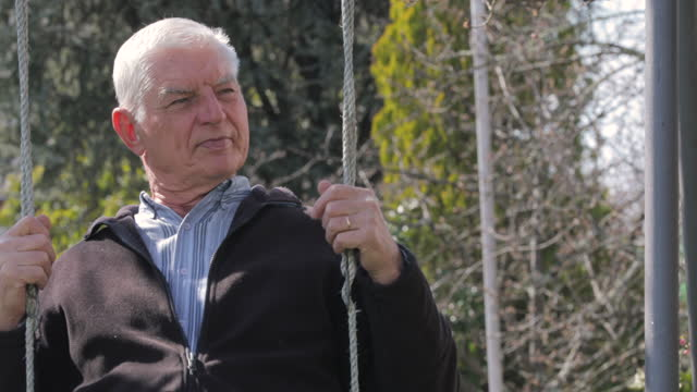 carefree senior man swinging in backyard - swinging stock videos & royalty-free footage