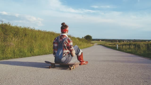 Carefree teenage girl listening to music with headphones on skateboard on sunny rural road,slow motion