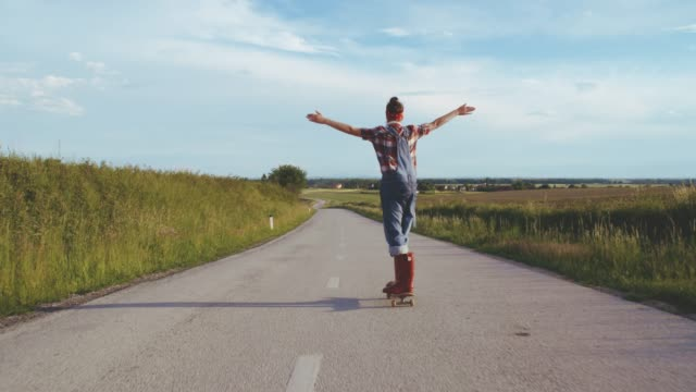 Carefree teenage girl skateboarding on sunny,rural road,slow motion