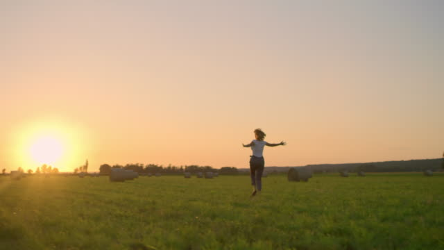 ms carefree woman dancing in idyllic,rural field with hay bales at sunset - hay field stock videos & royalty-free footage