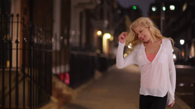 Carefree woman dancing to her own beat in the city at night
