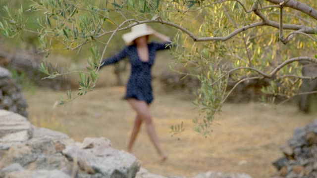 ms carefree woman skipping among idyllic olive trees - skipping along stock videos & royalty-free footage