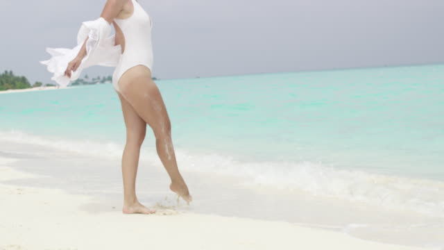 stockvideo's en b-roll-footage met ms carefree vrouw overslaan op zonnige tropische oceaan strand, maldiven - huppelen