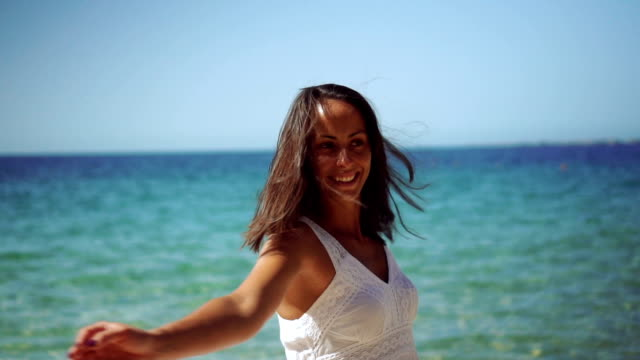 Zorgeloos vrouw ronddraaien op het strand
