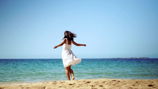 Carefree woman spinning around on the beach