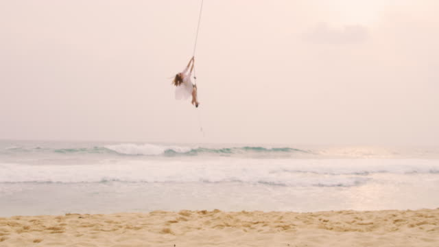 ms carefree woman swinging on rope swing over sandy ocean beach - rope swing stock videos & royalty-free footage