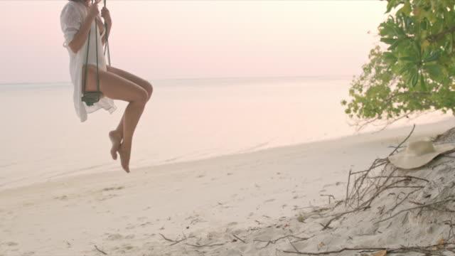 vidéos et rushes de femme de ms carefree balançant sur la plage de l'océan tropical, maldives - balançoire
