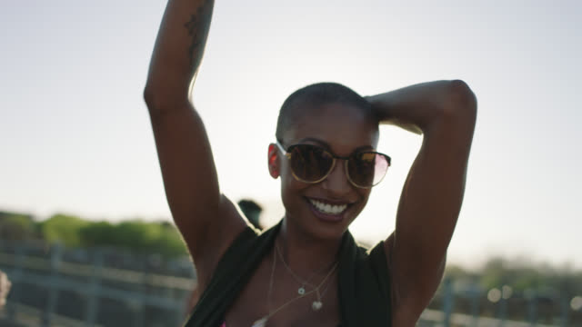 slo mo. carefree young african american woman looks at camera as she dances with friends to street music on pedestrian bridge in austin, texas. - passione video stock e b–roll