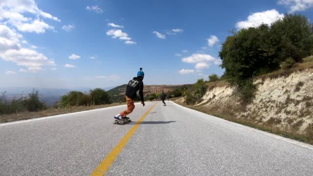 unbekümmerte junge männer longboard skating auf der kurvigen bergstraße - 25 29 jahre stock-videos und b-roll-filmmaterial