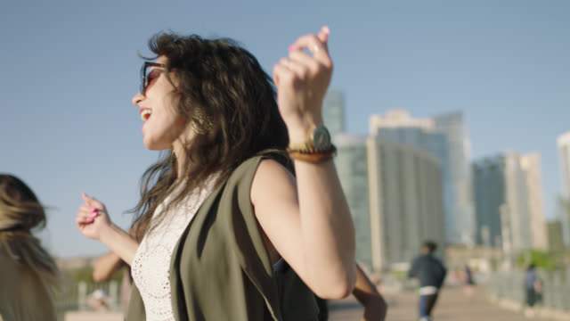 slo mo. carefree young woman cheers as she dances wildly with friends on pfluger pedestrian bridge with downtown austin skyline in background. - vita cittadina video stock e b–roll