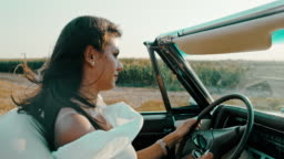 MS SLO MO Carefree young woman driving convertible along rural fields