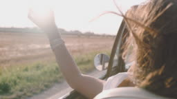 SLO MO Carefree young woman driving convertible along sunny, rural field
