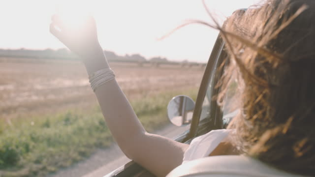 slo mo carefree young woman driving convertible along sunny, rural field - auto convertibile video stock e b–roll