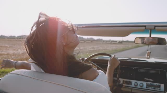 vídeos de stock e filmes b-roll de ms slo mo carefree young woman driving convertible along sunny, rural field - carro descapotável